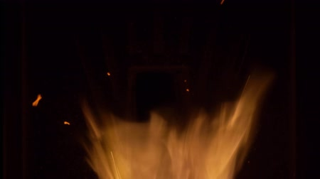 Close-up of warm cozy burning fire in a brick fireplace. Black background