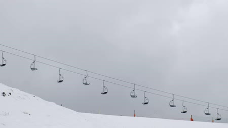 Video of chairlifts going down to snowy mountain on a ski resort on a cloudy day. Dostupné videozáznamy