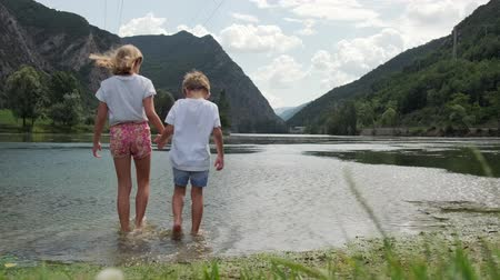 Video of two children holding hands while walking towards the mountain lake on a cloudy day. Dostupné videozáznamy