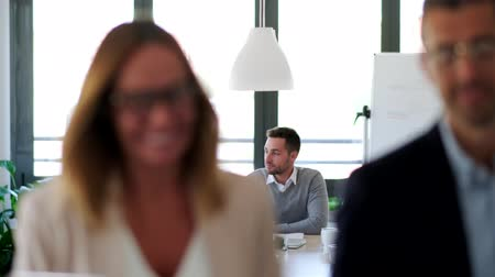Video of a woman and businessman talking while leaving the office. Behind, their partners continue to debate in the office. Vídeos