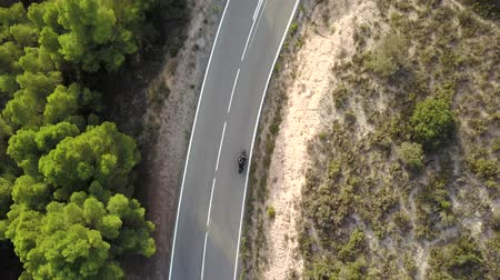 montar : Video of motorcyclist driving his motorbike on the mountain road in the country side. Aerial view.