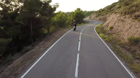 バイクに乗る人 : Video of motorcyclist driving his motorbike on the mountain road in the country side. Aerial view.