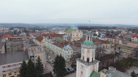 Aerial: flag waving while camera orbits with downtown. Aerial perspective. Sambor Ukraine