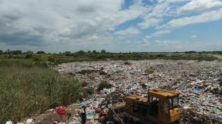 Aerial: tractor working at the garbage dump. Landfill, garbage dump, trash dump from above. Vídeos