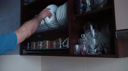The mans hand takes the plate from the cupboard and then puts it back. Close-up