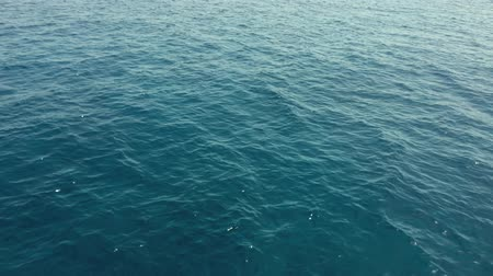 A Wake From a Ship at Sea with Blue Ocean Water, a Horizon, Blue Sky and Clouds.