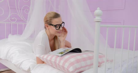 časopis : Beautiful young caucasian girl reading magazine in bed.