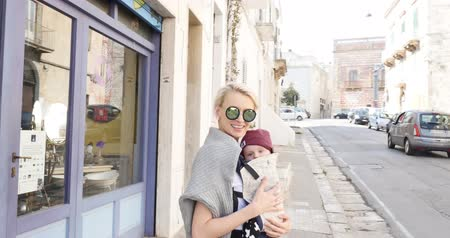 infante : Young beautiful caucasian mother walking with her baby in the city, smiling. Happy family leisure time.
