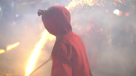 fireshow : fireshow on street, slow motion, blured. people in costumes of devils with torch