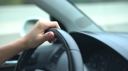 distraído : hand of the driver on the car steering wheel while driving on the highway