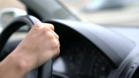 distraído : drivers hands while driving on a freeway close up.