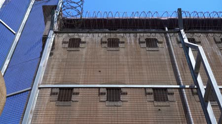Prison wall with small windows with bars and a high fence with barbed wire Stok Video