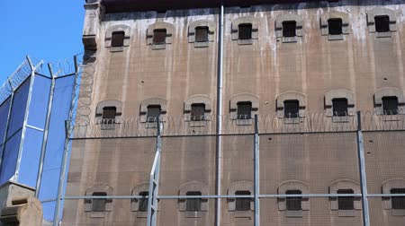 wall of the prison building with small windows with bars and a high fence