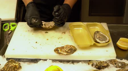 oysters : man cooks fresh oysters with lemon at the market. Stock Footage