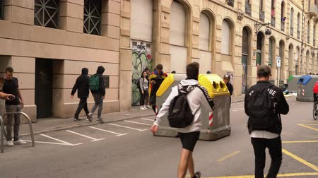 povstání : young people drag a dumpster along the road to build barricades during the riots