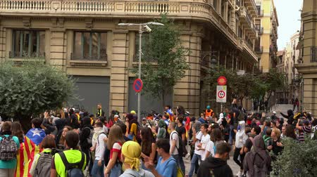 protestor : People with flags of Catalonia walk down the street during mass protests