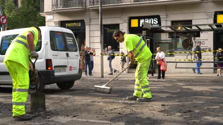 riot : road workers repairing a roadway against a burnt bus stop Stock Footage