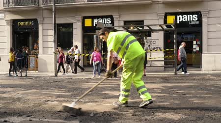 protestor : road workers repairing a roadway against a burnt bus stop Stock Footage
