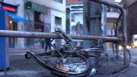 каталонский : burnt bike fastened to the fence, close up