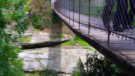 people go on a suspension bridge in the mountains. Stok Video