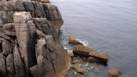 calm waves of the ocean beat against the rocks Stok Video