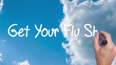 farmacologia : Get Your Flu Shot - concept with hand writing on the sky. Man writing. Blue sky with clouds time lapse.Words red circled. Business, technology, internet concept. Film look. 4k