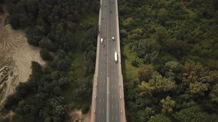 Aerial drone shot : View of vehicles crossing the long concrete bridge over a river;