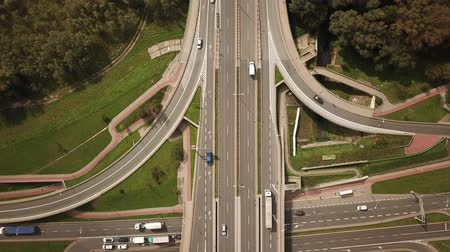 Aerial high drone flight over evening road traffic. Highway and overpass with cars and trucks, interchange, two-level road junction. Top view.; Dostupné videozáznamy