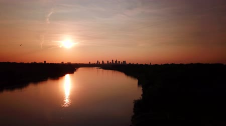Beautiful sunset to night transition over city of Warsaw downtown skyline. Over Vistula River. Drone flying up.;