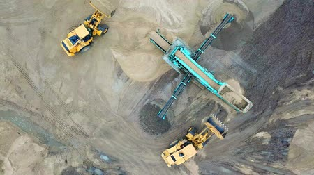 Sand mining industry. Bulldozer machine. Crawler bulldozer moving at sand mine. Mining machinery working at sand quarry. Drone view of mining equipment at industrial sand quarry. Earth mover;