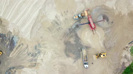яма : Excavator loader in sand quarry. View from above. Aerial view dumper trucks with cargo sand rides moving on territory sand factory. Tipper trucks on industrial area. Sand work; Стоковые видеозаписи