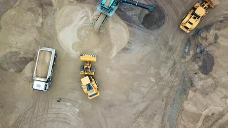 Aerial view loading bulldozer in open air quarry. Sand mining industry. Bulldozer machine. Crawler bulldozer moving at sand mine. Mining machinery working at sand quarry. Drone view of mining equipment at industrial sand quarry. Earth mover;