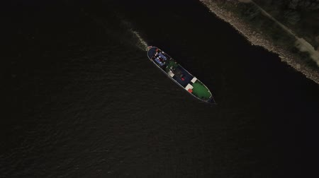 Video footage taken from birds eye view by drone of floating cruise boat. View from the top to the wide river,forest.;