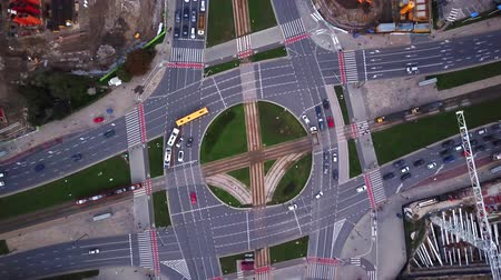 dik : Aerial city view, flying over a city, a suggestive perpendicular aerial video above a traffic roundabout with a lot of traffic;