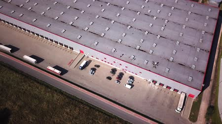 Zoom Out Aerial Shot of Industrial Warehouse Storage Building Loading Area where Many Trucks Are Loading Unloading Merchandise.