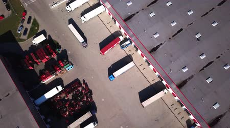 Zoom In Aerial Shot of Industrial Warehouse Storage Building Loading Area where Many Trucks Are Loading Unloading Merchandise.