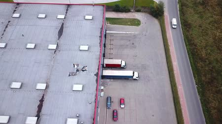 Aerial Shot of Industrial Warehouse Storage Building Loading Area where Many Trucks Are Loading Unloading Merchandise