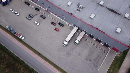 ithalat : Aerial Shot of Industrial Warehouse Storage Building Loading Area where Many Trucks Are Loading Unloading Merchandise
