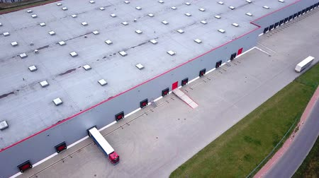 Moving Aerial Side Shot of Industrial Warehouse Loading Dock where Many Truck with Semi Trailers Load Unload Merchandise. Dostupné videozáznamy