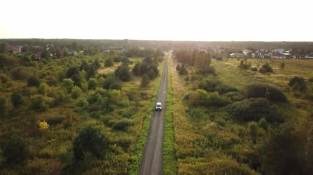 asfalt : Black SUV car driving along empty country highway in idyllic rural landscape. People on road trip journey across beautiful green Wideo