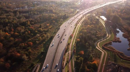4K AERIAL: Cars and semi truck driving on busy highway across the country in beautiful autumn evening. People on road trip traveling on busy freeway at golden sunset