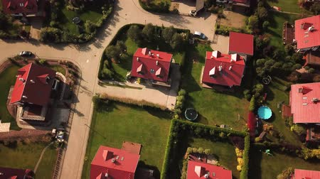 properties : Overhead right pan across houses, yards and cars along suburban street. Aerial shot 4k