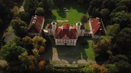 čeština : AERIAL front view of Castle. Flight over beautiful castle; located in landscape park with green trees forests in autumn. 4K