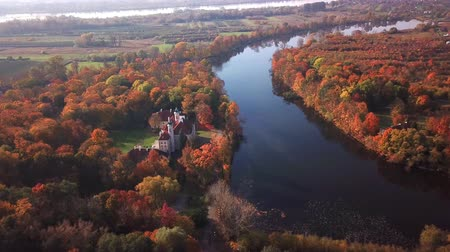 történelmi : Aerial View: Castle By The River.  Flight over beautiful castle; located in landscape park with green trees forests in autumn. 4K
