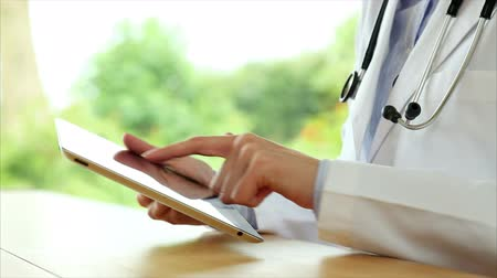 médicos : Tilt up shot of female doctors hands using digital tablet. Professional is scrolling and zooming. She is at wooden desk in brightly lit medical office.