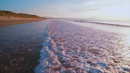 gibi : Idyllic aerial footage of tidal waves on sunny day.  Tracking shot of sea waves changing patterns as the calm. Beautiful view of serene ocean on sunny day.