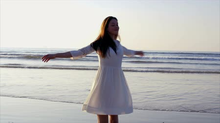 szépség a természetben : Happy woman turning and twirling around on beach,Slow motion video of happy young woman twirling around barefoot on beach. Beautiful female is enjoying nature at sea shore during sunset.