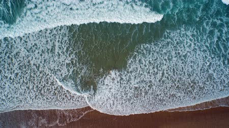 высота над уровнем моря : Aerial drone slow motion footage of ocean waves reaching shore. Lockdown shot of sea waves creating a texture from the white sea foam. The footage is filmed from an overhead perspective. HD 1080 video. Стоковые видеозаписи