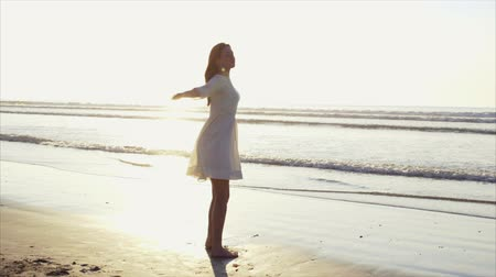 despreocupado : Tracking slow motion shot of carefree young woman twirling around on beach. Beautiful female is enjoying sea shore during sunset. Woman in white sundress is with arms outstretched.