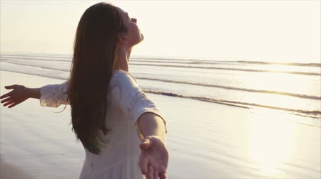 закат : Tilt up slow motion video of woman standing on wet shore. Side view of carefree female with arms outstretched and eyes closed. Woman in white sundress enjoying nature on beach during sunset. Стоковые видеозаписи